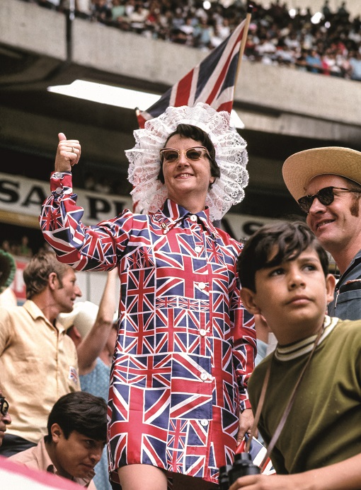 An England fan dressed in a Union Jack pattern dress looks on from the stands. (1970)